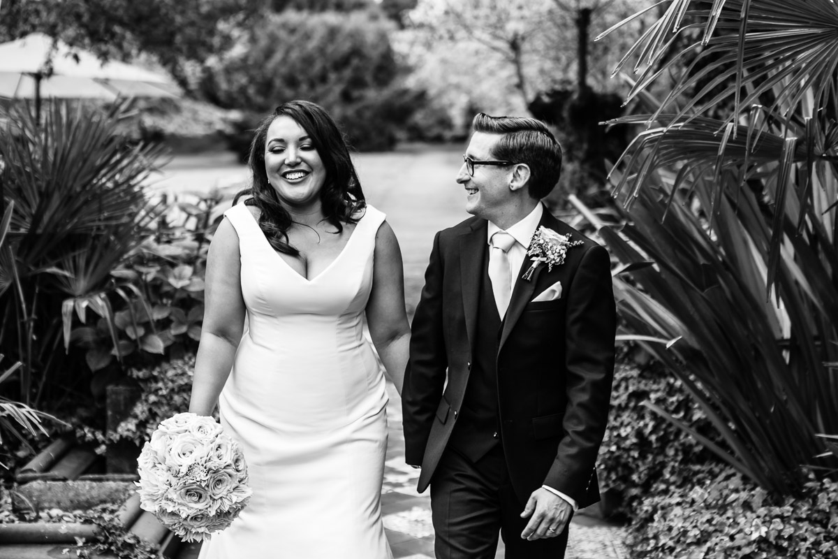A black and white image of a newlywed couple walking in a garden