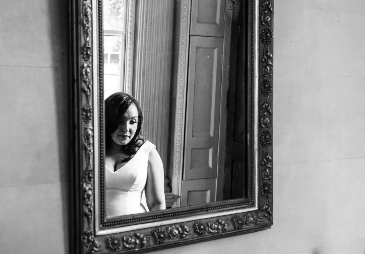 A black and white image of a bride reflected in a mirror on her wedding day.