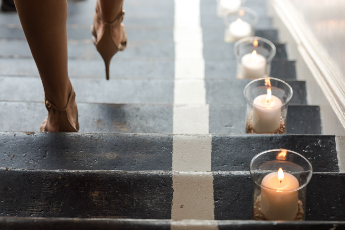 A low angle shot of high heeled shoes walking down a staircase lit by candles at a wedding