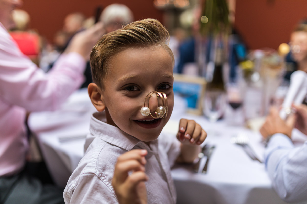 A shot of a young boy laughing at he camera as he has attached a napkin clip to his nose.