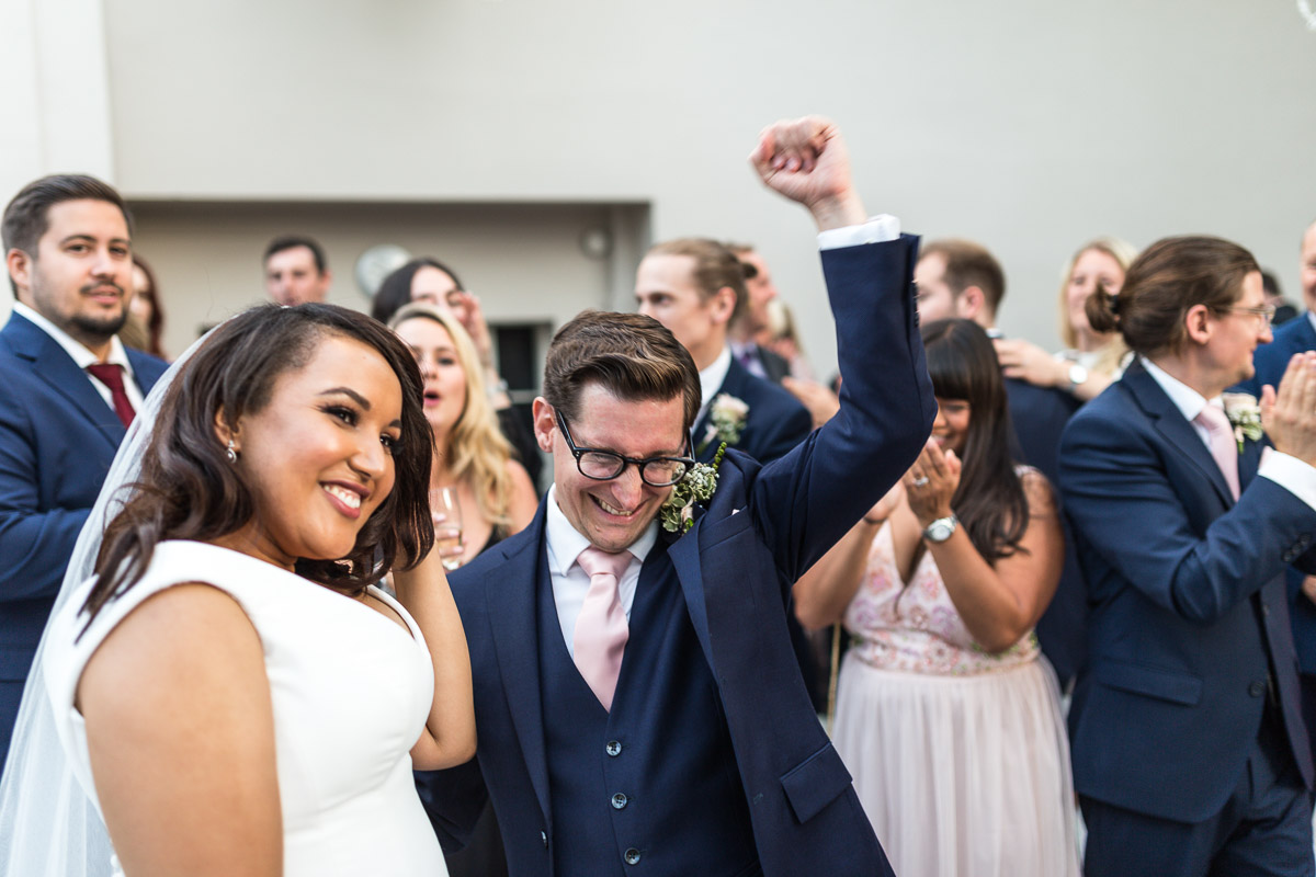 A groom pumps his fist in the air at the end of his first dance with his wife