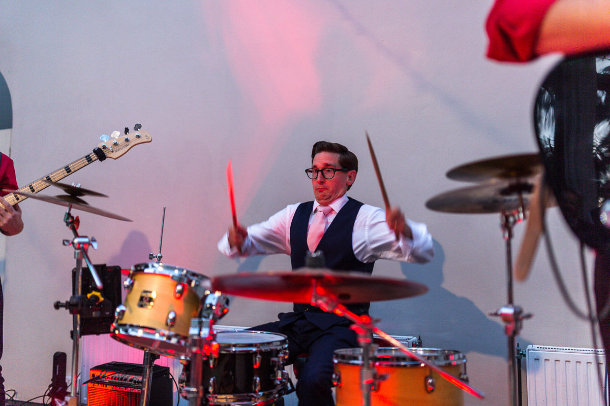 A groom playing drums at his own wedding reception