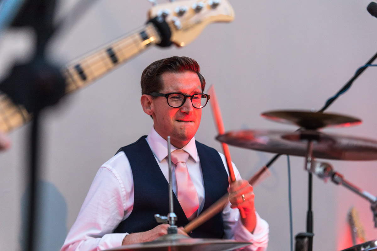 A close up of a groom playing drums at his wedding