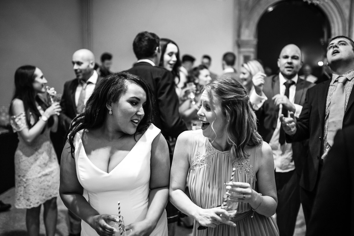 A black and white shot of a bride and bridesmaid dancing at her wedding