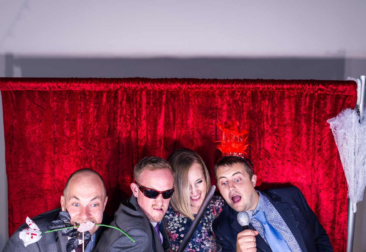 Wedding guests posing with props at a photo booth during a wedding reception