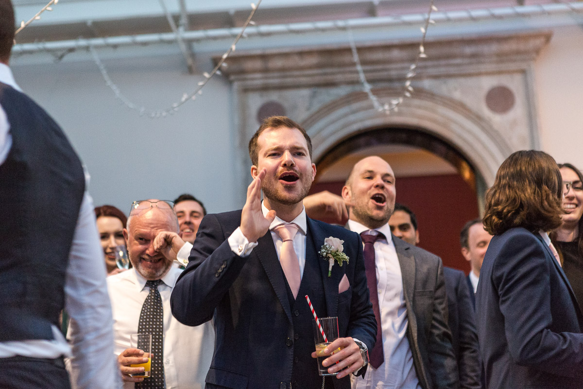 Guests cheer as they watch a groom performing in a band at a wedding