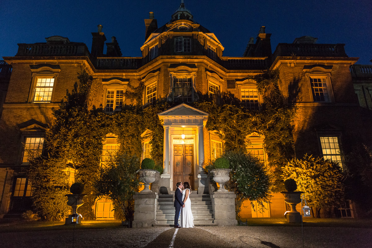 A wide shot of newlyweds stood in front of a lit up Hampton Court House at night.