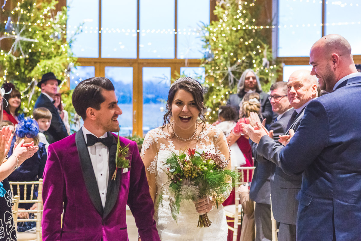 Newlyweds walk down the aisle smiling broadly