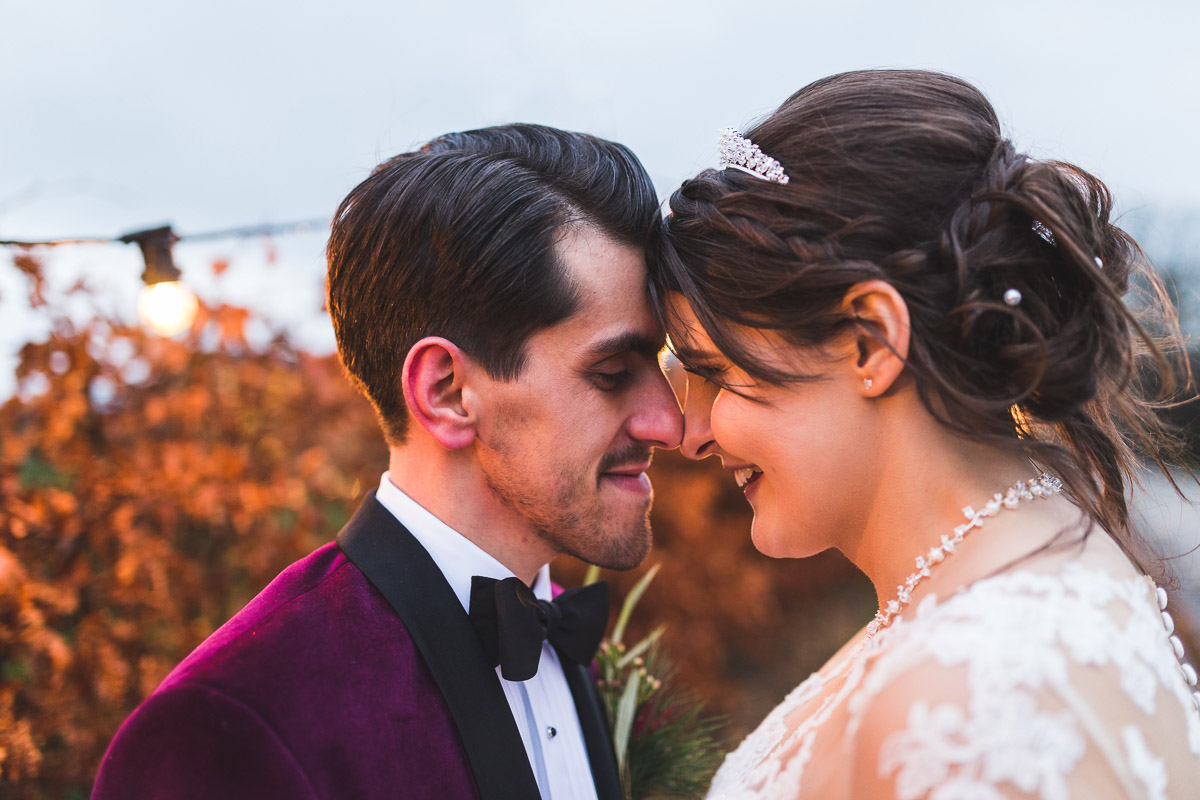 Newlywed couple touch foreheads while smiling