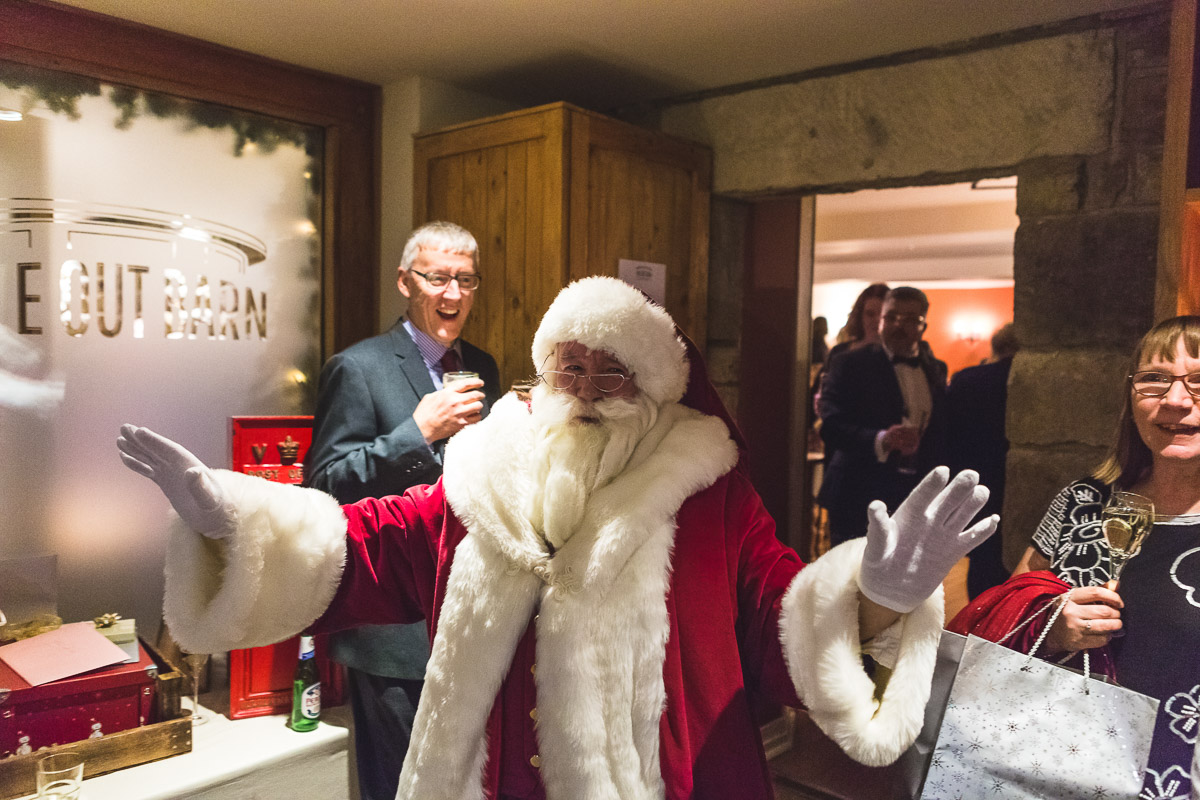 Santa Claus appears with his arms out at a wedding reception