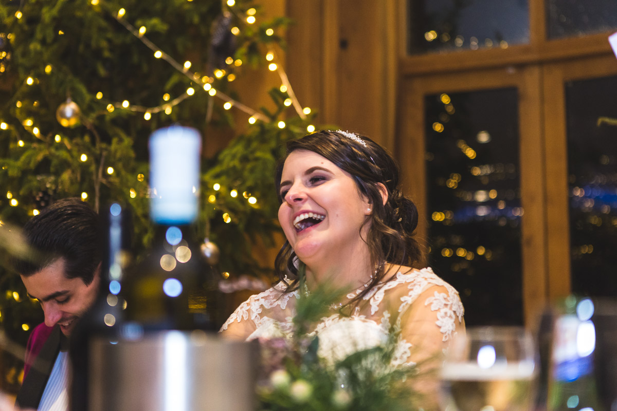 A flour shot of a bride laughing during the wedding speeches