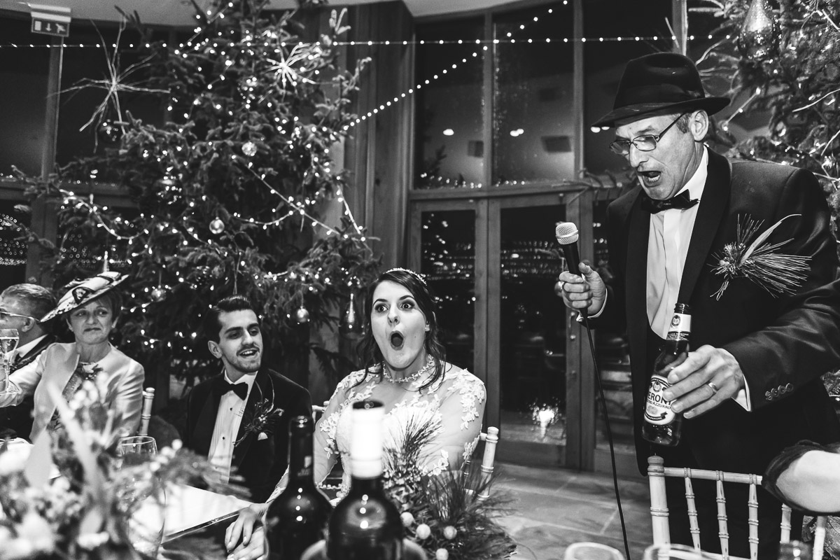 A mono image of the bride looking shocked during her father's wedding speech
