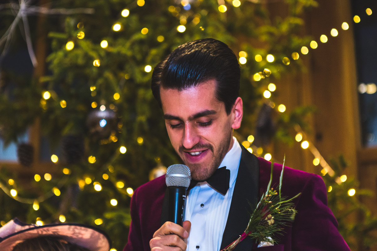 A close up of the groom smiling while holding a microphone