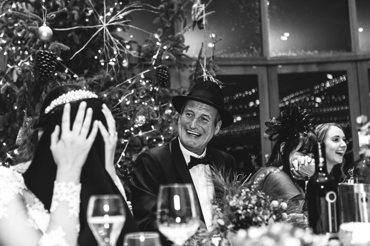 A black and white image of the bride covering her face during the wedding speeches