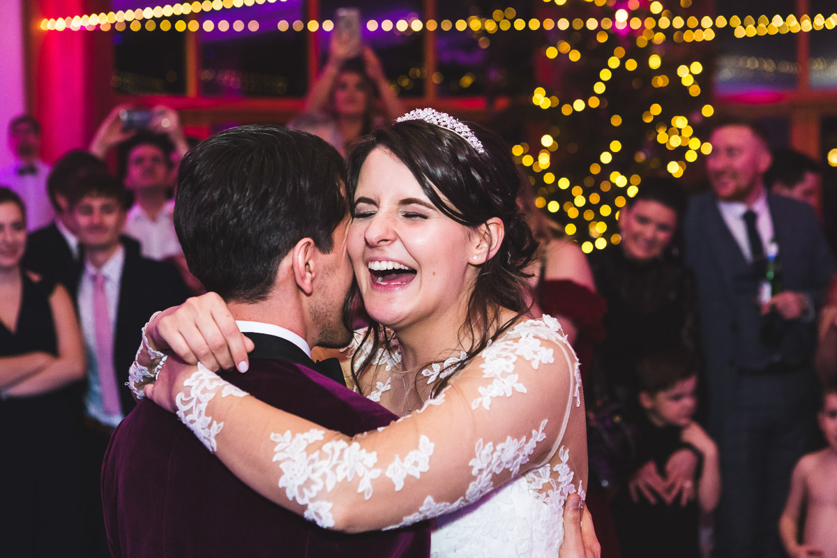 A bride laughs as she hugs her husband during their first dance