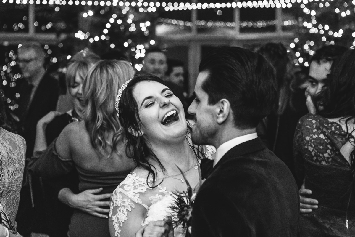 Black and white image of a bride laughing as she dances with her husband