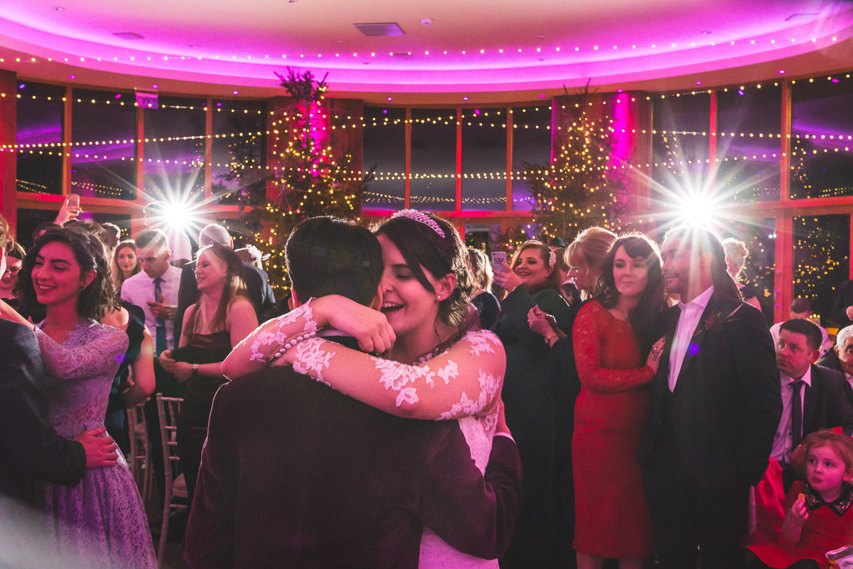 A bride embraces her husband surrounded by guest during their first dance at a wedding