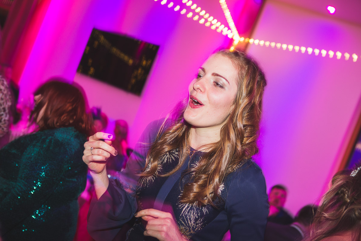 A young woman laughing as she dances at a wedding reception disco