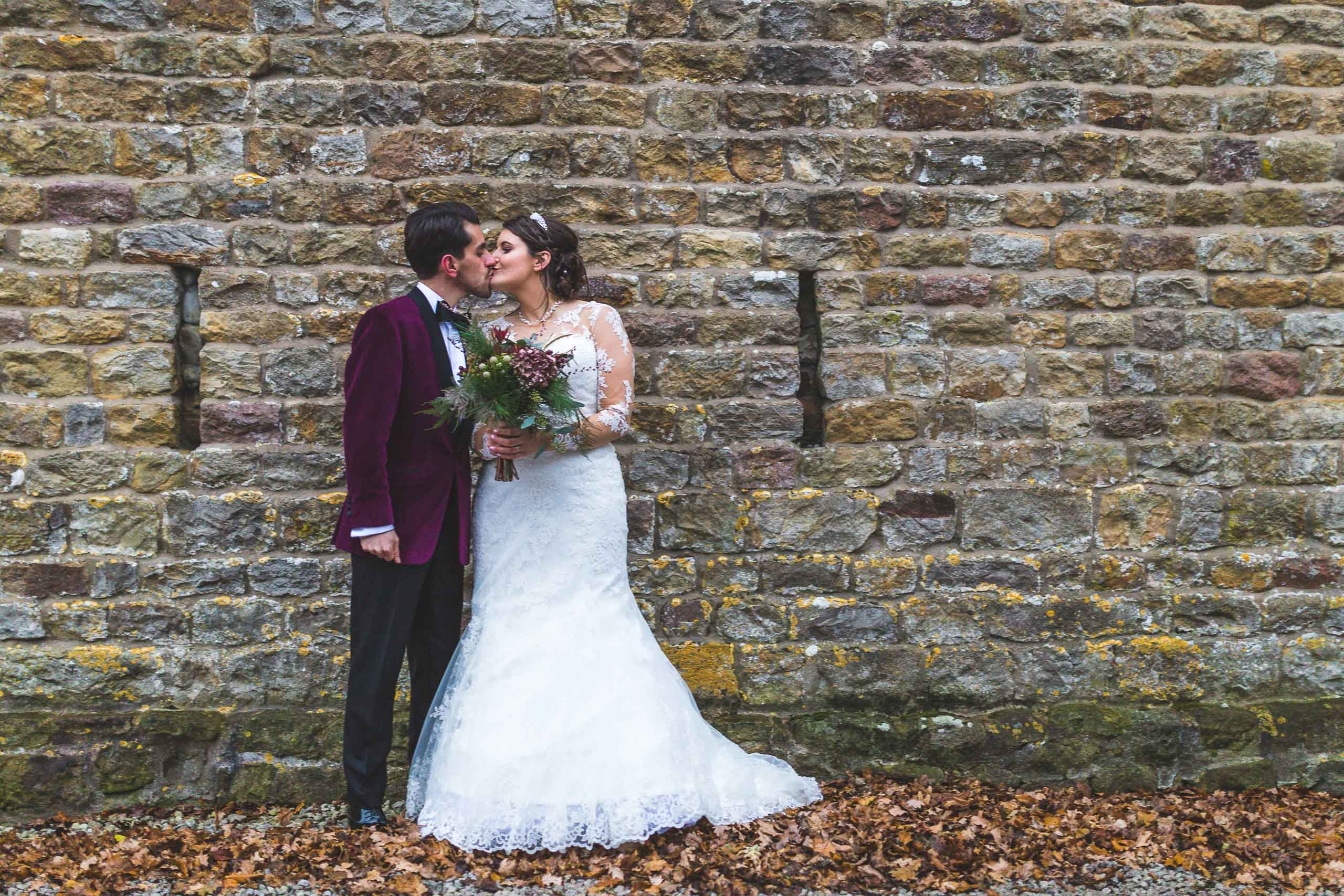 Newlyweds kiss while stood in front of a stone wall